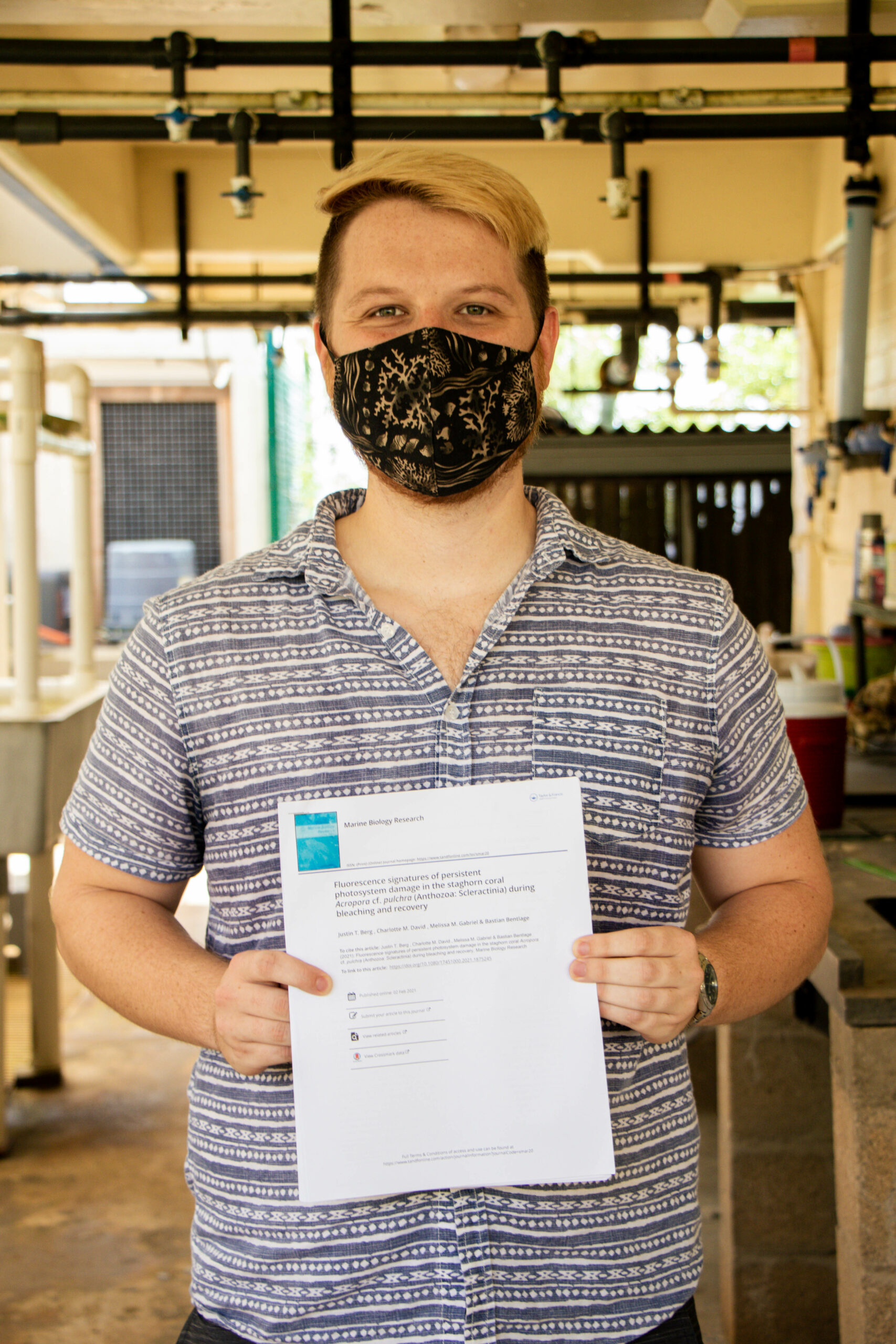 Graduate biology student Justin Berg holds his research paper that was published in the journal Marine Biology Research in February 2021.