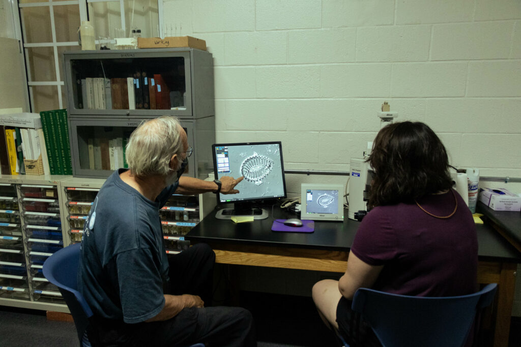 UOG Professor Emeritus of Biology Christopher Lobban and biology student and research fellow Gabriella Prelosky examine a single-celled algae under a microscope that they discovered in a mud sample from Yap. They are preparing research paper to document two diatoms that are potentially new species.